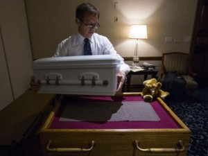 Glueckert Funeral Home Funeral Director John Glueckert lifts the casket containing the remains of an abandoned newborn baby on to a table in preparation for funeral and burial services in Arlington Heights, Illinois, June 19, 2015.  REUTERS/Jim Young